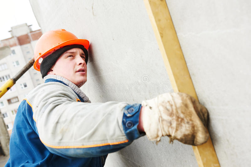 η κατασκευή απομόνωσε το συμπαθητικό εργαζόμενο εξαρτήσεων Οικοδόμος concreter με το επίπεδο στοκ φωτογραφία με δικαίωμα ελεύθερης χρήσης