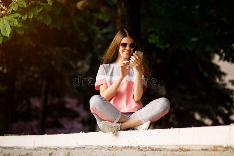 Η καυκάσια γυναίκα στα γυαλιά ηλίου που κάνει σερφ τον Ιστό με το τηλέφωνο, διάβασε τις καλές ειδήσεις, κουβεντιάζοντας το τηλέφω στοκ εικόνα με δικαίωμα ελεύθερης χρήσης