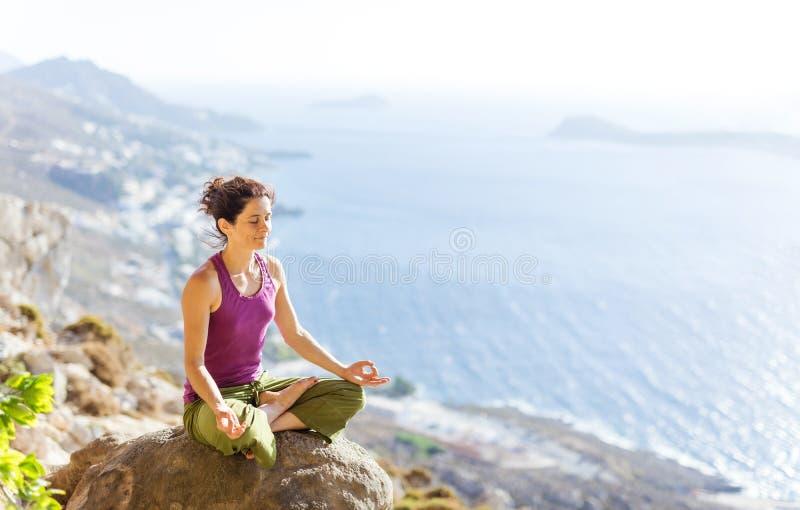 Η καυκάσια νέα γιόγκα άσκησης γυναικών καθμένος στο λωτό θέτει υπαίθρια στοκ εικόνες