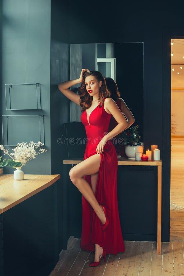 Η καυτή νέα ενήλικη υπερήφανη γυναίκα που φορά ένα μακρύ ερυθρό κόκκινο μακρύ φόρεμα καταδεικνύει σεξουαλικά το γυμνό χαριτωμένο  στοκ φωτογραφία με δικαίωμα ελεύθερης χρήσης