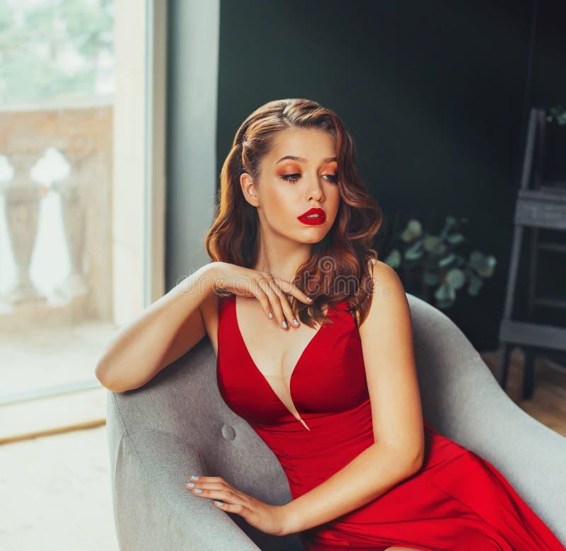 Η καυτή νέα ενήλικη, υπερήφανη και τυραννική γυναίκα, που ντύνεται σε ένα μακρύ ερυθρό κόκκινο μακρύ φόρεμα, κρατά σεξουαλικά το  στοκ εικόνες με δικαίωμα ελεύθερης χρήσης