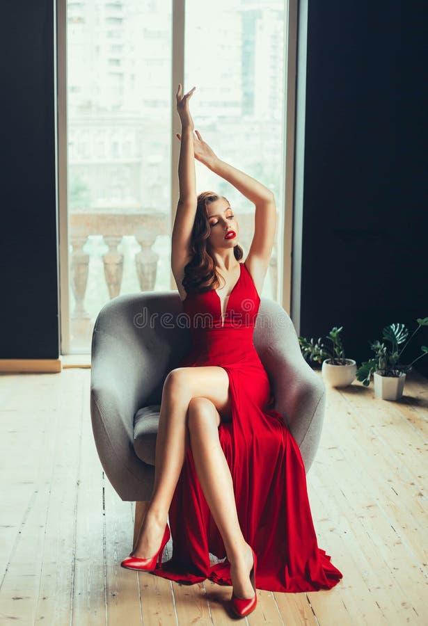 Η καυτή νέα υπερήφανη γυναίκα, έντυσε σε ένα μακρύ ερυθρό κόκκινο μακρύ φόρεμα και κόκκινα ψηλοτάκουνα παπούτσια Ήπια αυξάνει τα  στοκ εικόνες