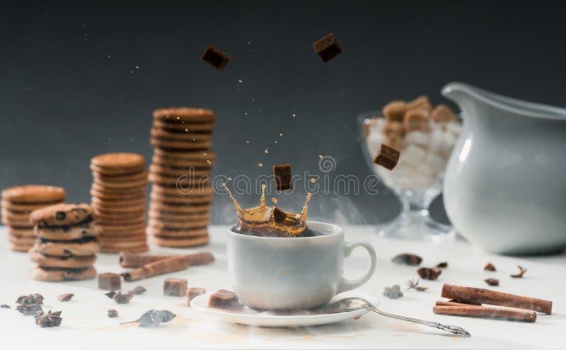 Η καφετιά ζάχαρη κυβίζει την πτώση στο φλυτζάνι με το μαύρο καφέ στον πίνακα με τα μπισκότα στοκ εικόνες με δικαίωμα ελεύθερης χρήσης