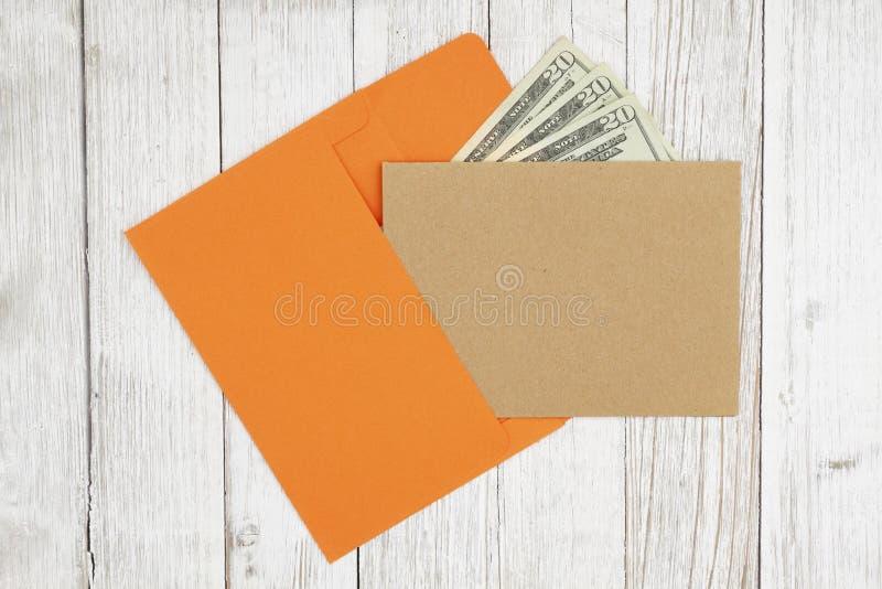 Η καφετιά κενή ευχετήρια κάρτα με το φάκελο με τα χρήματα σε κατασκευα στοκ εικόνες