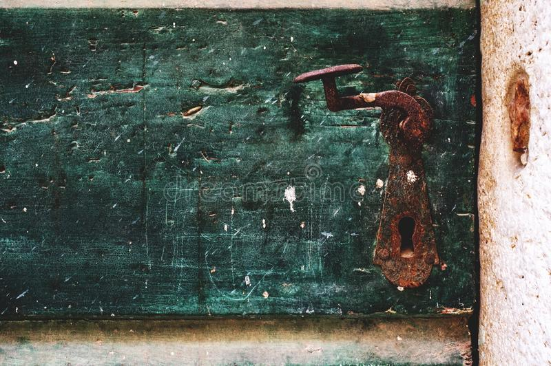 Η καφετιά λαβή μετάλλων καλύπτεται με τη σκουριά στην παλαιά πράσινη πόρτα Παλαιός προσδιορισμός r Θόρυβος στοκ φωτογραφία