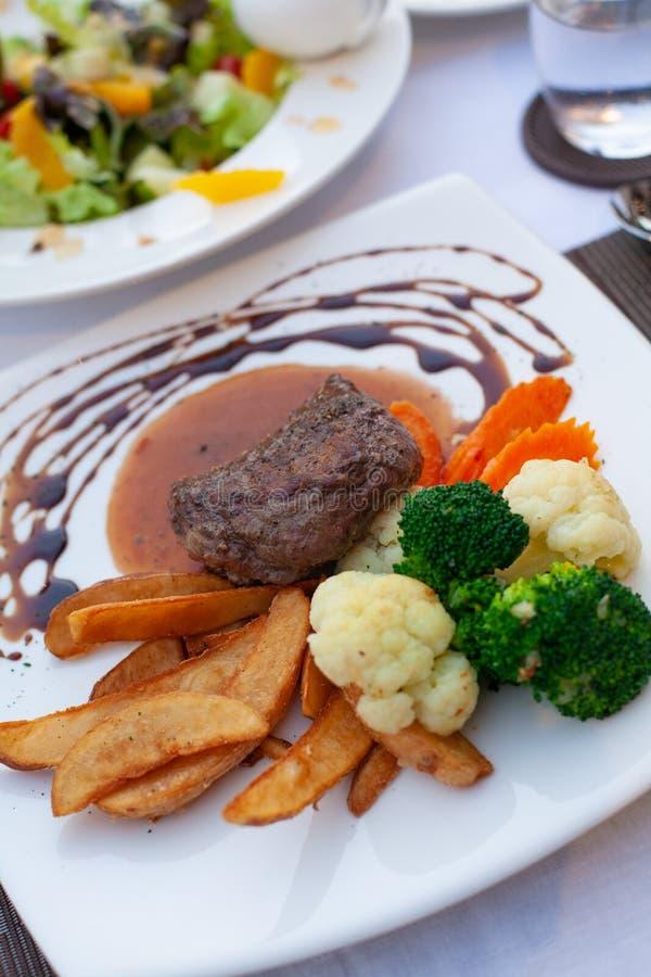 Η καφετιά σάλτσα μπριζόλας βόειου κρέατος εξυπηρέτησε με το λαχανικό και τα τηγανητά σε ένα συμπαθητικό πιάτο στοκ φωτογραφίες