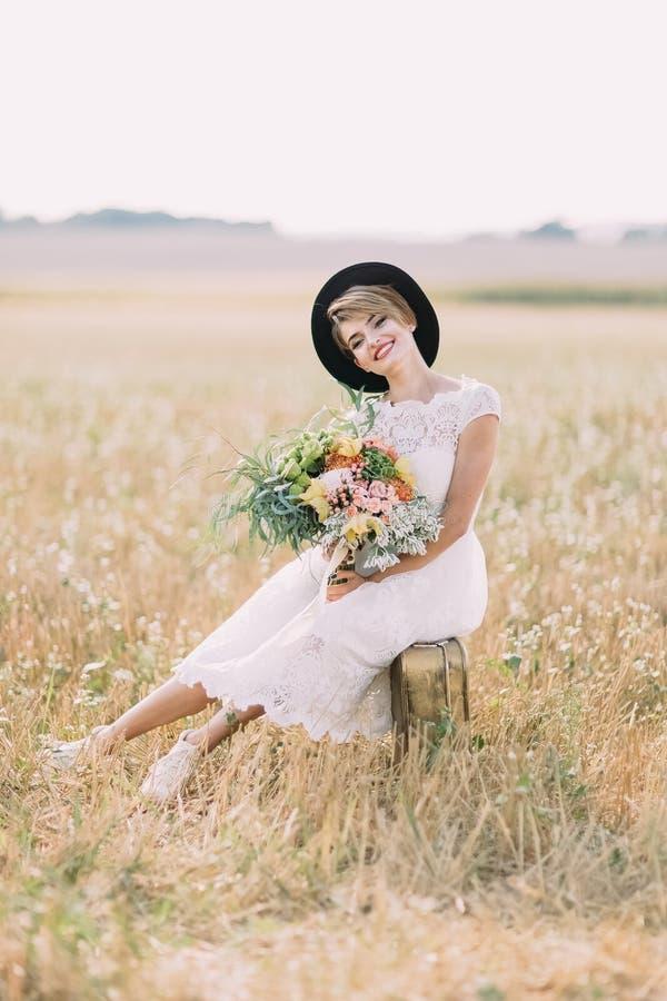 Η καλή νύφη στο γαμήλιο φόρεμα γόνατο-μήκους κρατά τη ζωηρόχρωμη ανθοδέσμη και κάθεται στην εκλεκτής ποιότητας βαλίτσα στοκ φωτογραφία με δικαίωμα ελεύθερης χρήσης