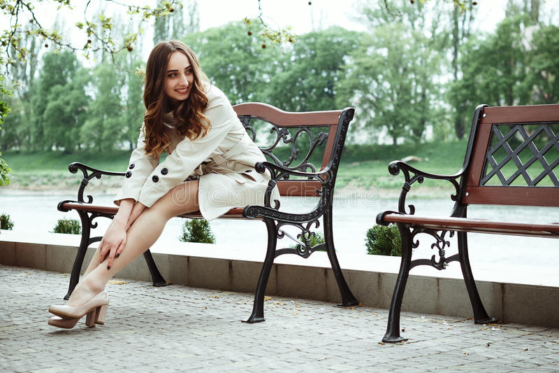 Η καλό όμορφο γυναίκα ή το κορίτσι σε ένα ελαφρύ αδιάβροχο κάθεται σε ένα ben στοκ φωτογραφία με δικαίωμα ελεύθερης χρήσης