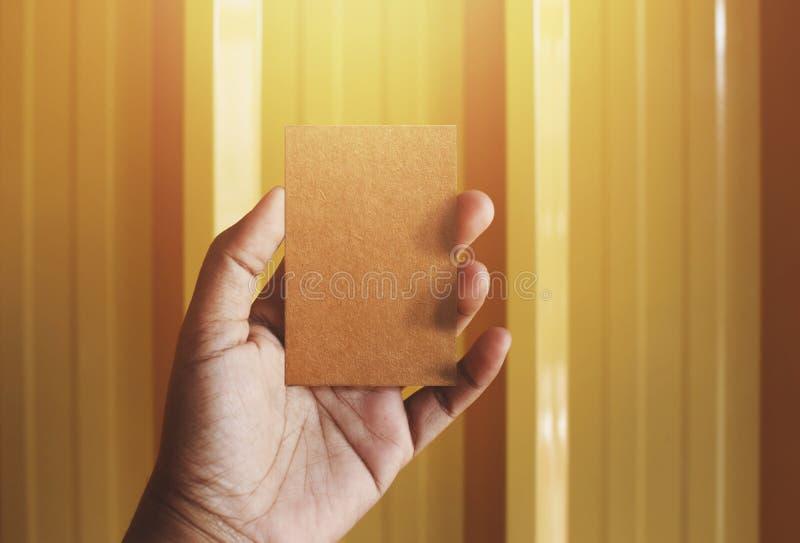 Η κενή επαγγελματική κάρτα εγγράφου τεχνών εκμετάλλευσης χεριών για τη χλεύη επάνω, στοκ φωτογραφία με δικαίωμα ελεύθερης χρήσης