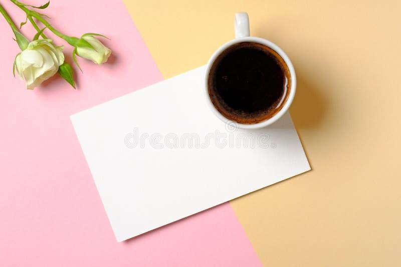 Η κενή κάρτα εγγράφου με το διάστημα αντιγράφων, το φλιτζάνι του καφέ και τα άσπρα τριαντάφυλλα ανθίζει στο ζωηρόχρωμο υπόβαθρο Έ στοκ εικόνες