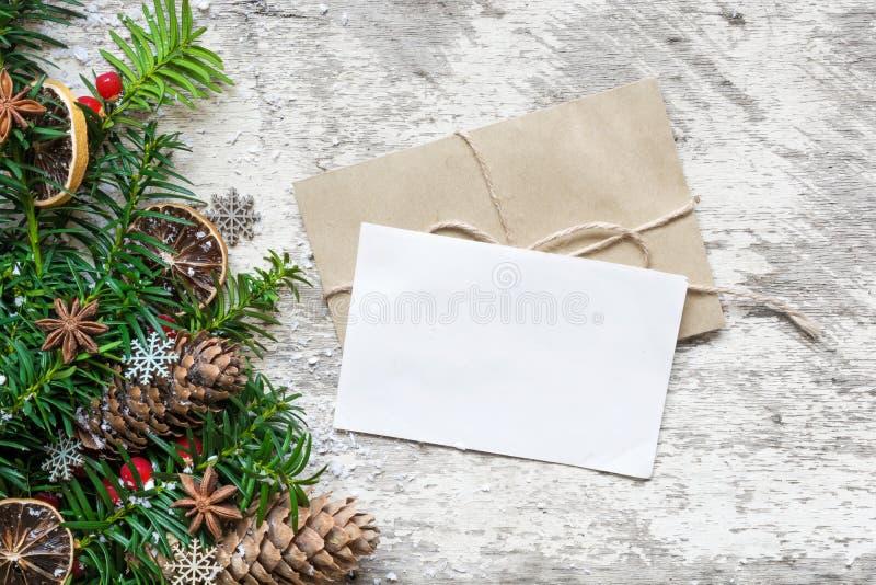 Η κενοί άσπροι ευχετήρια κάρτα και ο φάκελος Χριστουγέννων με το δέντρο έλατου διακλαδίζονται, διακοσμήσεις τροφίμων και κώνοι πε στοκ φωτογραφία