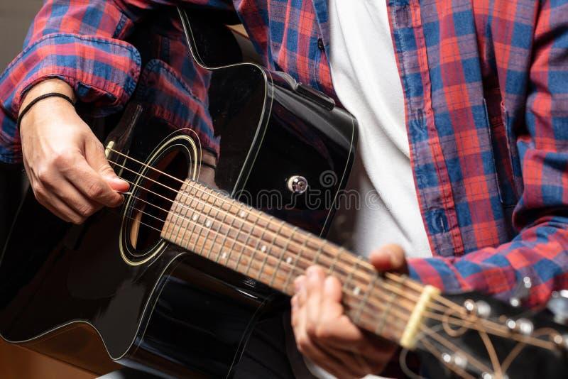 Η κιθάρα παιχνιδιού νεαρών άνδρων, κλείνει επάνω την άποψη στοκ φωτογραφία με δικαίωμα ελεύθερης χρήσης