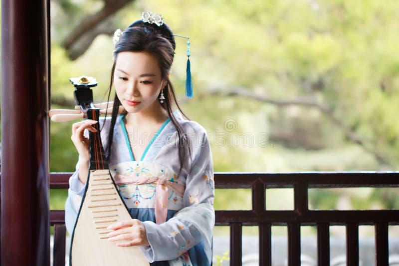 Η κινεζική γυναίκα στο παραδοσιακό φόρεμα Hanfu, παίζει το παραδοσιακό όργανο του pipa στοκ φωτογραφία με δικαίωμα ελεύθερης χρήσης