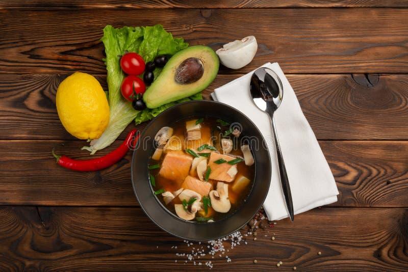 Η κινεζική σούπα με τα κόκκινα ψάρια στο Μαύρο καλύπτει σε ένα ξύλινο υπόβαθρο στοκ φωτογραφία με δικαίωμα ελεύθερης χρήσης
