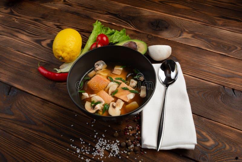 Η κινεζική σούπα με τα κόκκινα ψάρια στο Μαύρο καλύπτει σε ένα ξύλινο υπόβαθρο στοκ εικόνα με δικαίωμα ελεύθερης χρήσης