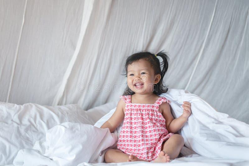Η κινηματογράφηση σε πρώτο πλάνο ένα μικρό κορίτσι κάθεται το γέλιο στο κρεβάτι στο υπόβαθρο κρεβατοκάμαρων στοκ φωτογραφία με δικαίωμα ελεύθερης χρήσης