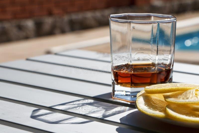 Η κινηματογράφηση σε πρώτο πλάνο ενός γυαλιού εδροτόμησε πολύτιμους λίθους το γυαλί με ένα ισχυρό οινοπνευματώδες ποτό που στέκετ στοκ φωτογραφία με δικαίωμα ελεύθερης χρήσης