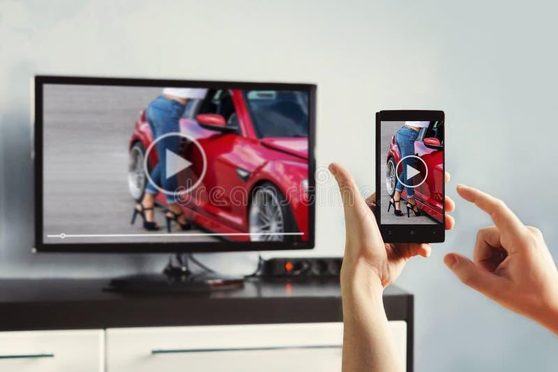 Η κινηματογράφηση σε πρώτο πλάνο στο smartphone εκμετάλλευσης χεριών γυναικών και χρησιμοποιεί app με τον τηλεχειρισμό στοκ εικόνα με δικαίωμα ελεύθερης χρήσης