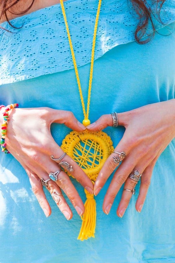 Η κινηματογράφηση σε πρώτο πλάνο της νέας γυναίκας παραδίδει τη μορφή καρδιών με το μέρος boho θερινής άνοιξης κοσμήματος, δαχτυλ στοκ φωτογραφία με δικαίωμα ελεύθερης χρήσης