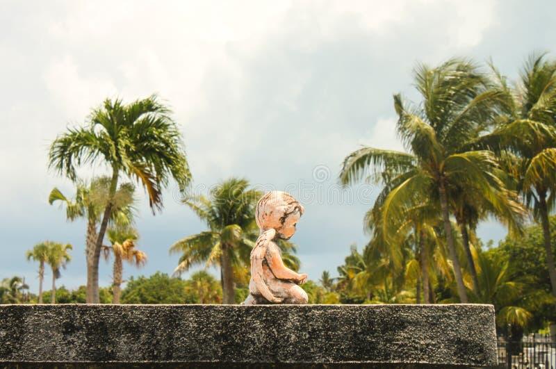 Η κινηματογράφηση σε πρώτο πλάνο του αγάλματος αγγέλου μωρών που γονατίζει σε έναν τάφο με τους ψηλούς φοίνικες πίσω στοκ φωτογραφία με δικαίωμα ελεύθερης χρήσης