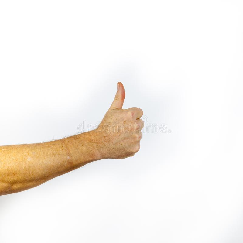 Η κινηματογράφηση σε πρώτο πλάνο του αρσενικού χεριού που παρουσιάζει αντίχειρες υπογράφει επάνω ενάντια στο άσπρο backgr στοκ εικόνες με δικαίωμα ελεύθερης χρήσης