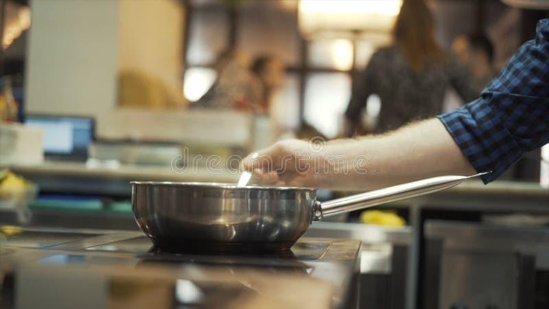 Η κινηματογράφηση σε πρώτο πλάνο του αρχιμάγειρα παραδίδει ένα μπλε ελεγμένο πουκάμισο προετοιμάζοντας κάποιο πιάτο σε μια κουζίν στοκ εικόνες
