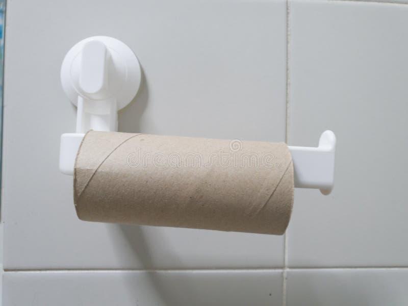Η κινηματογράφηση σε πρώτο πλάνο του τελειωμένου ρόλου χαρτιού τουαλέτας στο λουτρό Κενός ρόλος στον κάτοχο χαρτιού τουαλέτας με  στοκ φωτογραφία