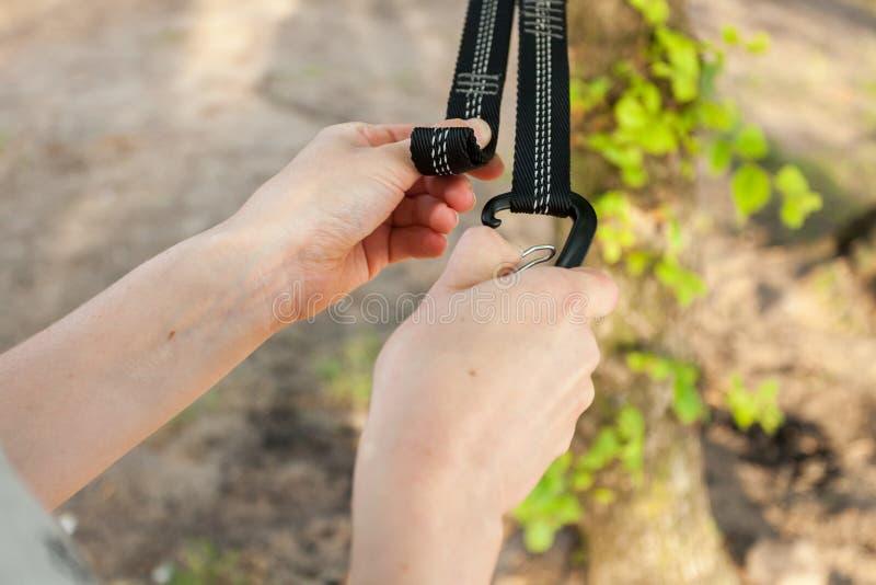 Η κινηματογράφηση σε πρώτο πλάνο των χεριών γυναικών συνδέει τα λουριά αιωρών στο δέντρο στοκ φωτογραφία