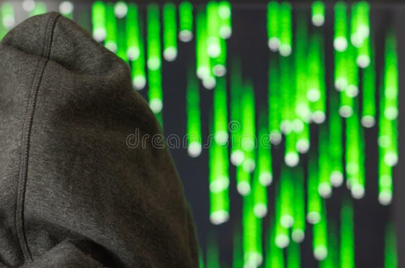 Η κινηματογράφηση σε πρώτο πλάνο, χάκερ στην κουκούλα εξετάζει το όργανο ελέγχου, η έννοια της ασφάλειας υπολογιστών στοκ φωτογραφία