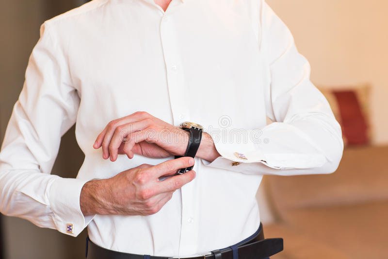 Η κινηματογράφηση σε πρώτο πλάνο του ατόμου βάζει σε ένα ρολόι στοκ φωτογραφία με δικαίωμα ελεύθερης χρήσης