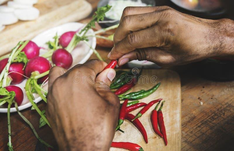 Η κινηματογράφηση σε πρώτο πλάνο των χεριών με το πιπέρι τσίλι προετοιμάζεται να μαγειρεψει στοκ φωτογραφίες