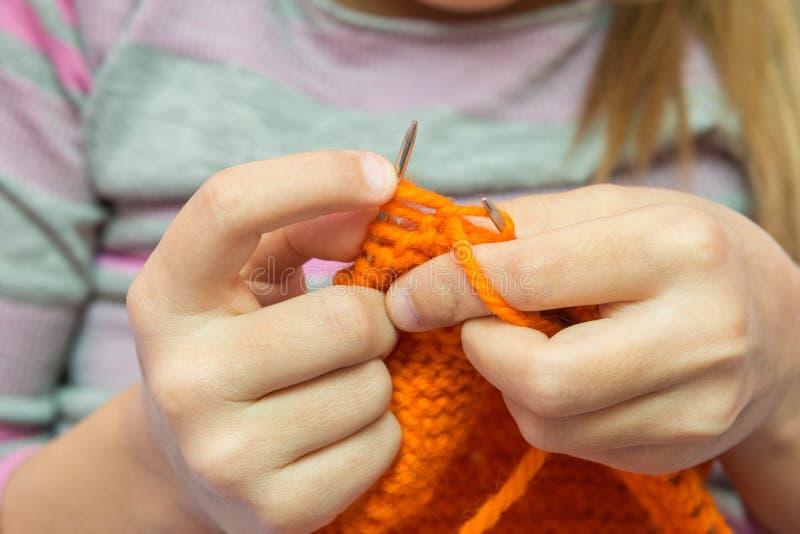 Η κινηματογράφηση σε πρώτο πλάνο των χεριών παιδιών πλέκει με τις βελόνες στοκ εικόνες