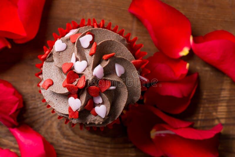 Η κινηματογράφηση σε πρώτο πλάνο Cupcake με το πάγωμα σοκολάτας και αυξήθηκε πέταλα στοκ εικόνες με δικαίωμα ελεύθερης χρήσης