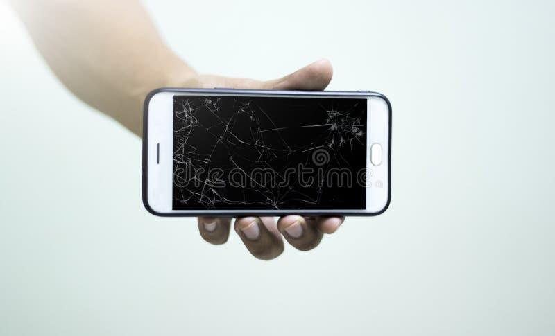 Η κινητή τηλεφωνική οθόνη έχει μια πλήρη ρωγμή του λευκού στα χέρια των ανθρώπων στοκ εικόνες με δικαίωμα ελεύθερης χρήσης