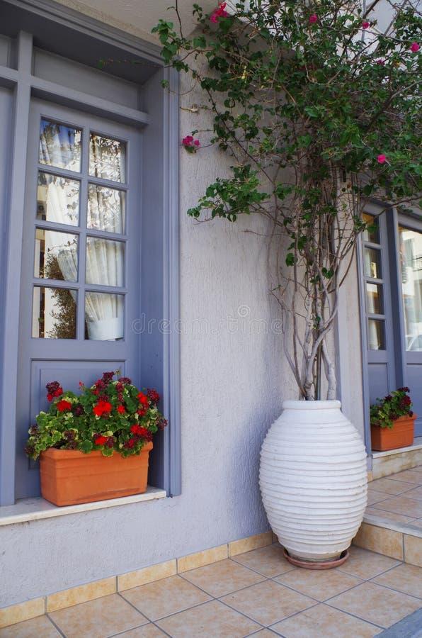 Η κλασσική αρχιτεκτονική των ελληνικών πόλεων, του πορφυρών παραθύρου και της πόρτας στα άσπρα κτήρια και τα λουλούδια στην είσοδ στοκ εικόνα