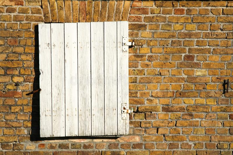 Η κλειστή άσπρη ξύλινη πόρτα παραθύρων με το οξυδωμένο μέταλλο αρθρώνει σε έναν βρώμικο κίτρινο κοκκινωπό τουβλότοιχο μιας παλαιά στοκ φωτογραφία με δικαίωμα ελεύθερης χρήσης