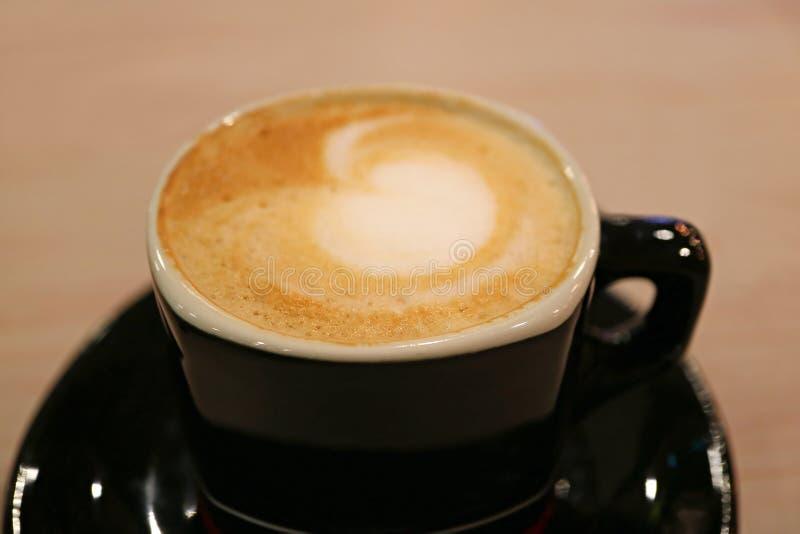 Η κλειστή επάνω καρδιά διαμόρφωσε τον αφρό γάλακτος του καφέ Cappuccino σε ένα μαύρο φλυτζάνι στοκ φωτογραφία με δικαίωμα ελεύθερης χρήσης