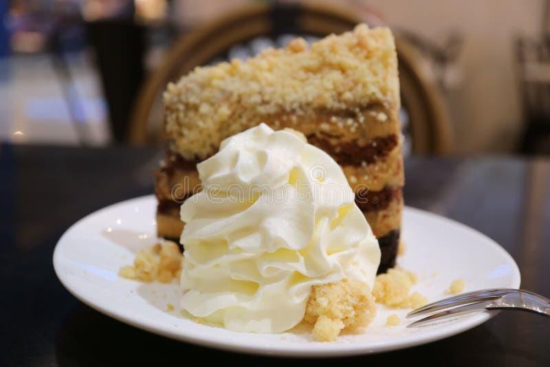 Η κλειστή επάνω χνουδωτή κτυπημένη κρέμα εξυπηρέτησε με το γλυκό και αρωματικό κέικ πιτών banoffee στοκ εικόνα