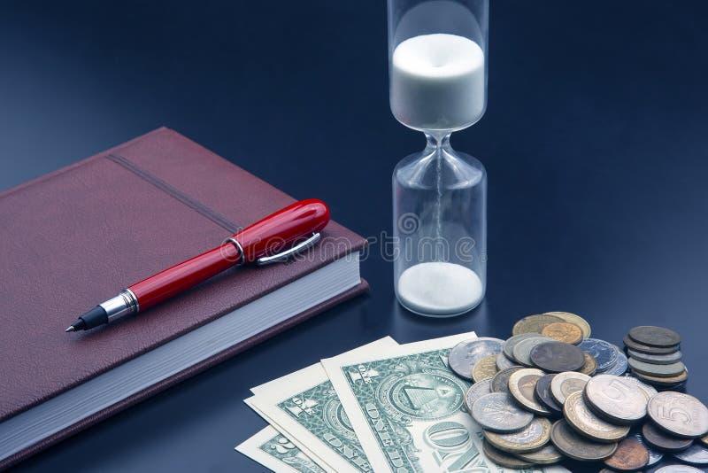 Η κλεψύδρα, τα χρήματα, η γραφίδα και ο φορητός υπολογιστής βρίσκονται στο τραπέζι Στοιχεία γραφείου επιχειρήσεων Ο χρόνος είναι  στοκ εικόνες
