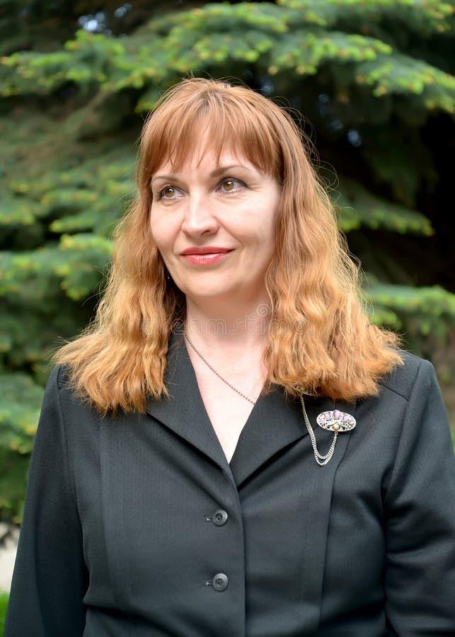 Η κοκκινομάλλης γυναίκα σε ένα μαύρο σακάκι κοιτάζει κατά μέρος στοκ εικόνα