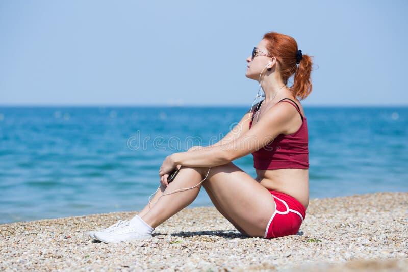 Η κοκκινομάλλης νέα γυναίκα sportswear κάθεται στην παραλία χαλικιών στοκ φωτογραφίες