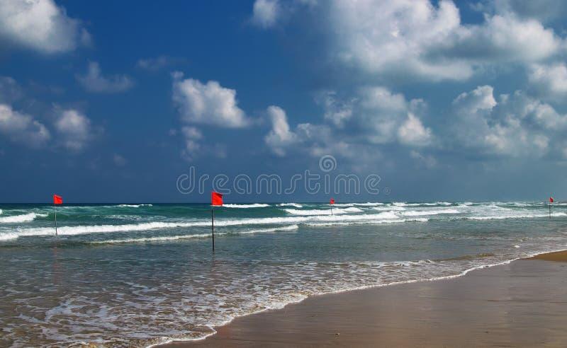 Η κολύμβηση είναι επικίνδυνη στα κύματα θάλασσας Κόκκινο χτύπημα σημαιών προειδοποίησης στον αέρα στο θυελλώδη καιρό στοκ εικόνες με δικαίωμα ελεύθερης χρήσης