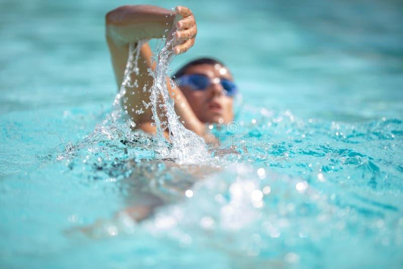 Η κολύμβηση κολυμβητών ατόμων σέρνεται σε μια μπλε λίμνη νερού στοκ εικόνες
