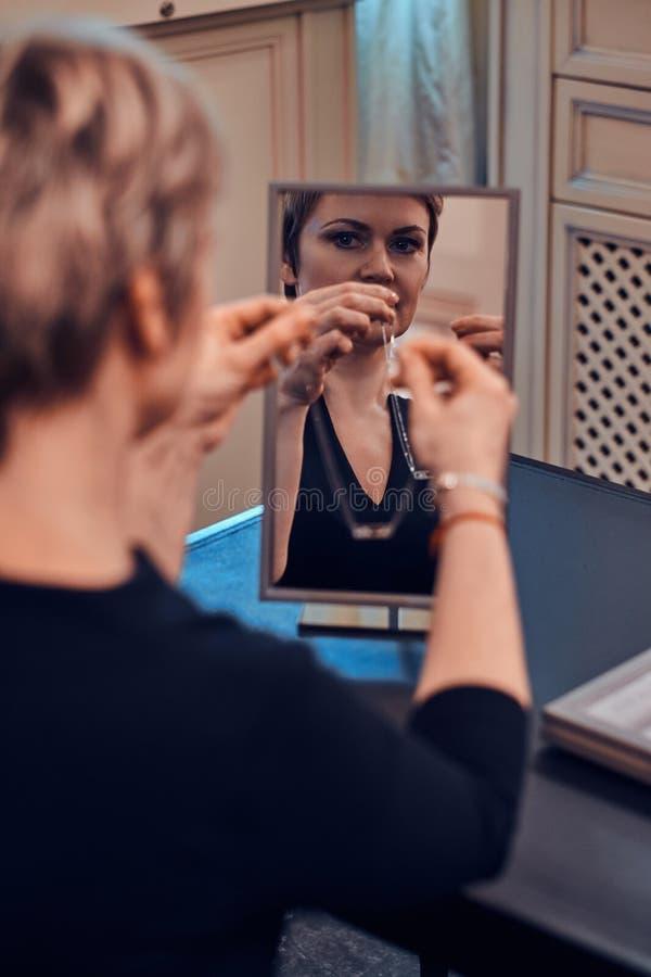 Η κομψή γυναίκα προσπαθεί στο νέο περιδέραιο κοσμημάτων μπροστά από τον καθρέφτη στοκ εικόνα