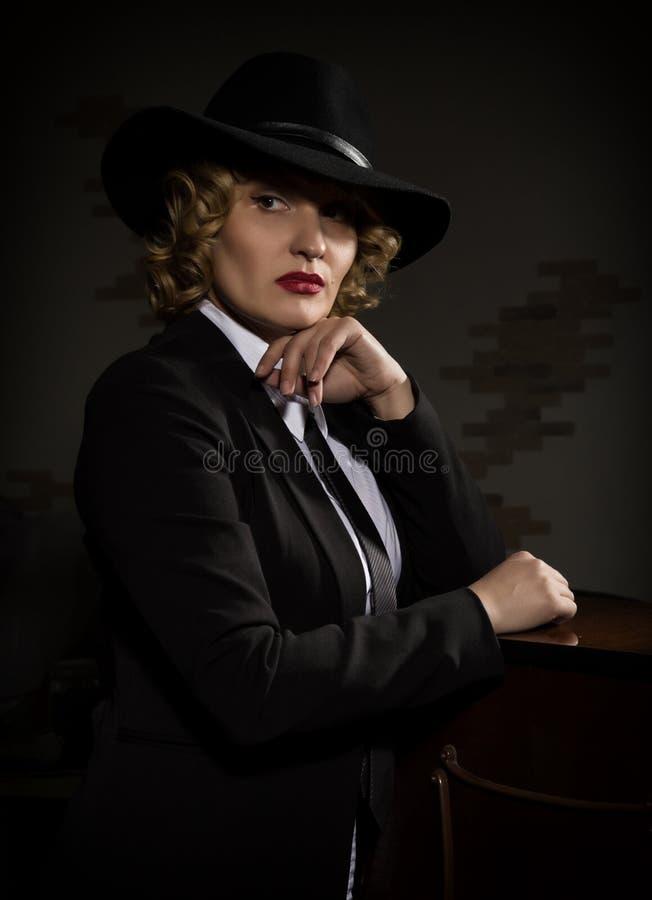 Η κομψή γυναίκα στο επιχειρησιακό κοστούμι με ένα καπέλο θέτει σε ένα σκοτεινό υπόβαθρο, τυποποιημένο αναδρομικό πορτρέτο στοκ φωτογραφίες