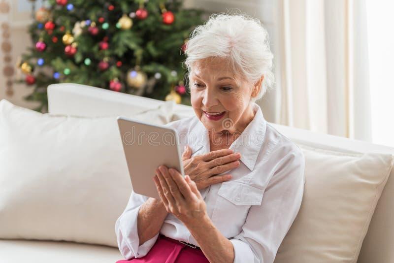 Η κομψή ηλικιωμένη γυναίκα διαβάζει τις ειδήσεις χρησιμοποιώντας τις σύγχρονες τεχνολογίες στοκ φωτογραφία με δικαίωμα ελεύθερης χρήσης