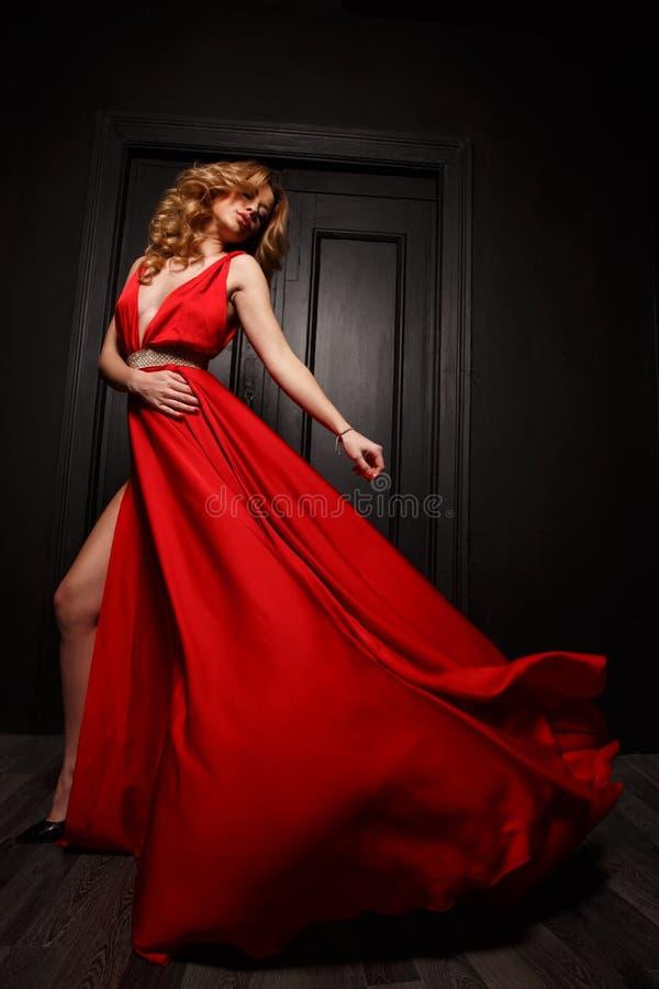 Η κομψή και εμπαθής γυναίκα βασίλισσας στο κόκκινο κυματίζοντας φόρεμα βραδιού είναι σύλληψη στην κίνηση, η ξύλινη πόρτα είναι στ στοκ εικόνες