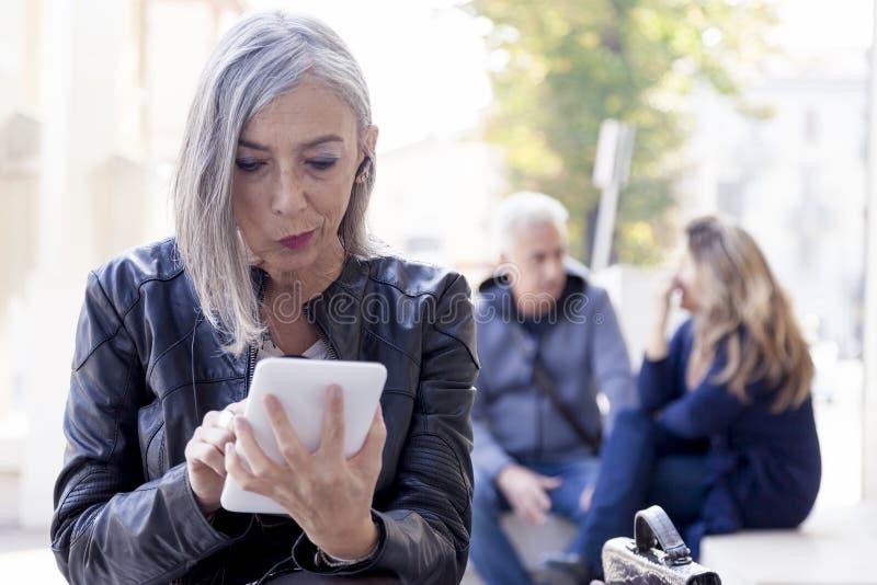 Η κομψή κυρία συμβουλεύεται το έξυπνο τηλέφωνο στοκ φωτογραφία με δικαίωμα ελεύθερης χρήσης