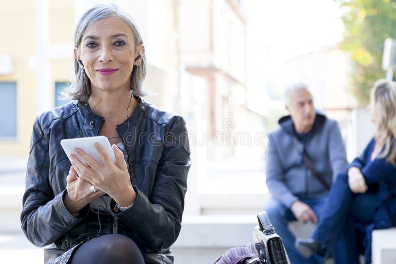 Η κομψή κυρία συμβουλεύεται το έξυπνο τηλέφωνο στοκ εικόνες