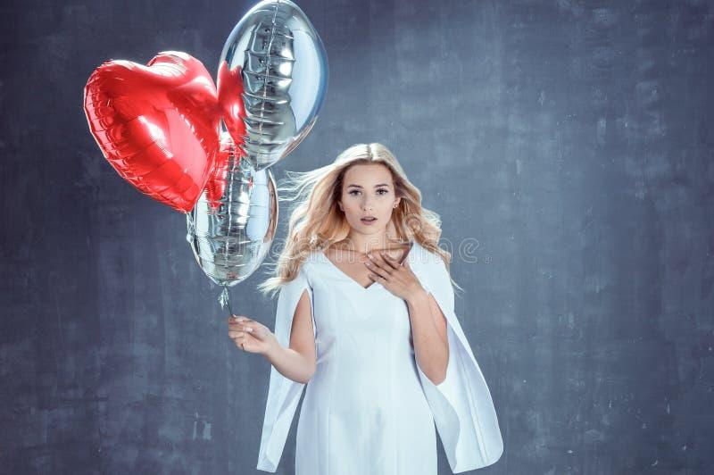 Η κομψή ξανθή γυναίκα κρατά τα καρδιά-διαμορφωμένα μπαλόνια στοκ φωτογραφία με δικαίωμα ελεύθερης χρήσης